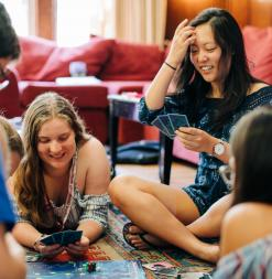 In the dorm, participants play a card game together on the floor.